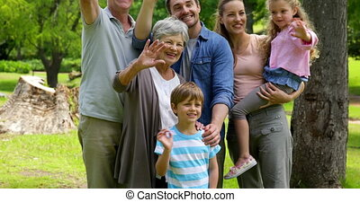 Multi generation family posing and waving at camera in a...