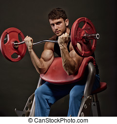 athletic young man lifting weights