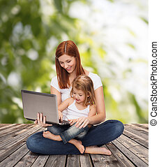 happy mother with adorable little girl and laptop -...