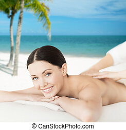 smiling woman in spa salon getting massage - spa, resort and...
