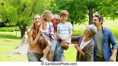 Multi generation family posing and laughing at camera in a...