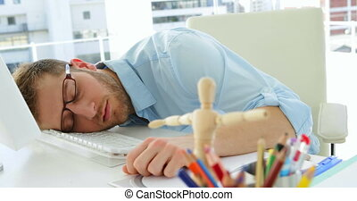 Attractive businessman sleeping in his office