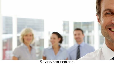 Businessman smiling in front of his team in the office