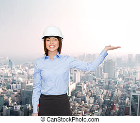 businesswoman in helmet holding something on palm -...