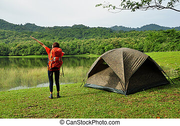Young woman camping near the lake