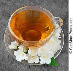 Tea with white flowers of jasmine on wooden texture.