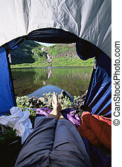 Woman lying in tent with a view of lake