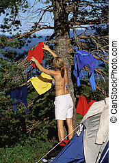Young woman hanging out washing on a tree next to campsite