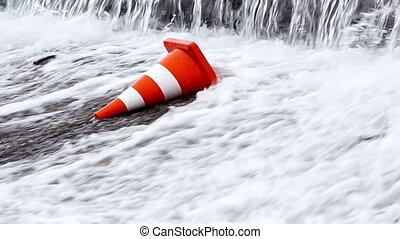 Water drops on an orange traffic cone. Slow-motion