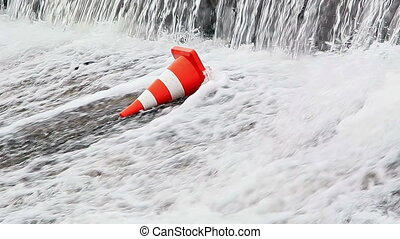 Water flows on the orange traffic cone