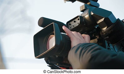 Professional camera - Man filming outdoors with a...