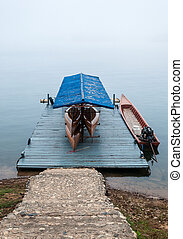 Wooden boat house in the early morning with fog.