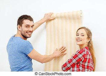 smiling couple choosing wallpaper for new home - repair,...
