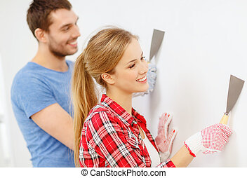 smiling couple doing renovations at home - repair,...