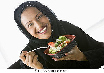 A Middle Eastern woman holding a salad up to the camera