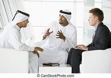 A meeting between a Caucasian businessman and two Middle...