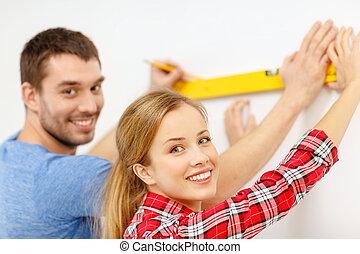 couple building using spirit level to measure - repair,...