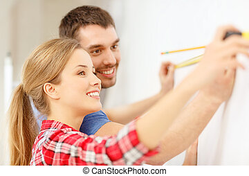 smiling couple measuring wall - repair, building and home...