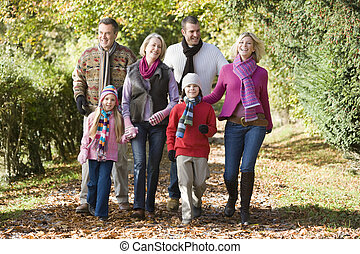 Multi-generation family on walk through woods -...