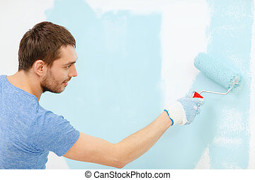 smiling man painting wall at home - repair, building and...
