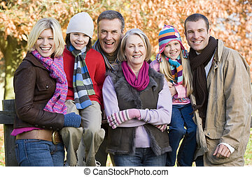 Multi-generation family on autumn walk sitting on fence