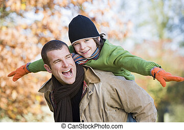Father giving son piggyback in autumn woodland