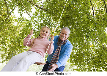 Grandfather pushing granddaughter on swing - Grandfather...