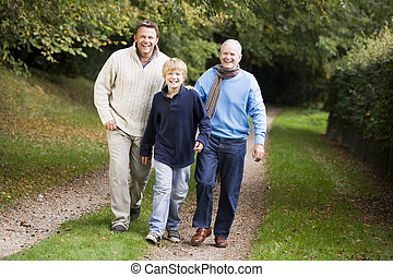 Grandfather walking with son and grandson