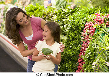 Mother and daughter choosing fresh produce