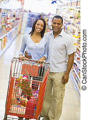 Couple grocery shopping - Young couple grocery shopping in...