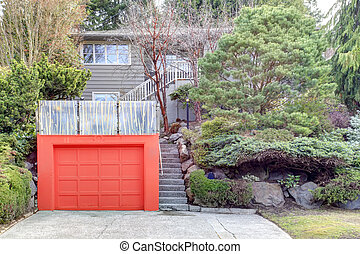 Clapboard siding house on a hill. Red door garage with roof...