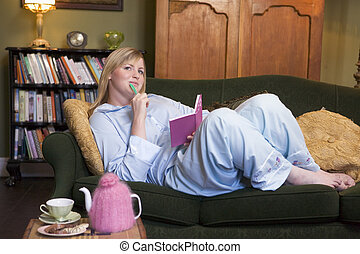 A young woman lying on her couch writing in her journal