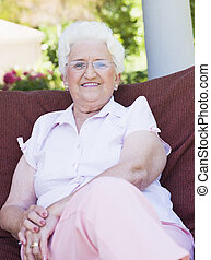 Senior woman sitting on garden chair smiling to camera