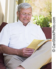 Senior man relaxing with book
