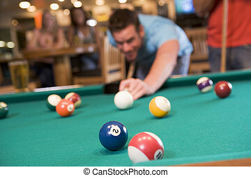 Young man playing pool in a bar focus on pool table