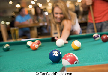 Young woman playing pool in a bar focus on pool table