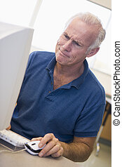 Mature male student frowning at computer monitor