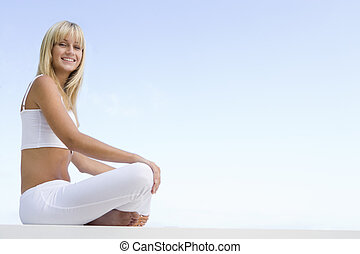Young woman relaxing outdoors against blue sky