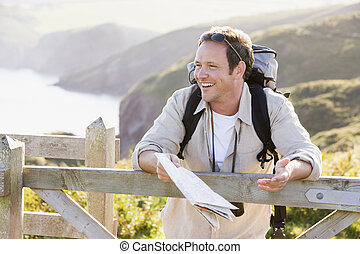 Man relaxing on cliffside path holding map and laughing