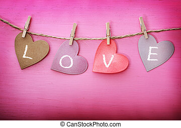 Love message on paper hearts over pink wooden board