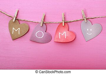 Mothers day message on paper hearts over pink wooden board