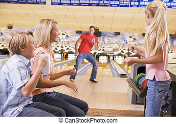 Family in bowling alley smiling