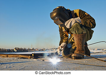 welder at construction site - welder working with electrode...