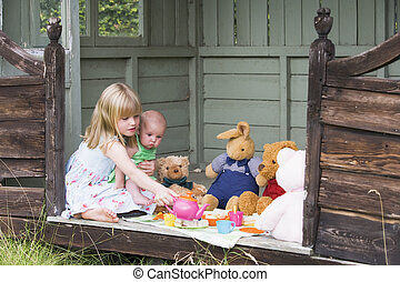Young girl in shed with baby playing tea