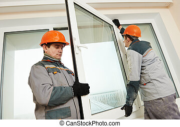 two workers installing window - Two male industrial builders...