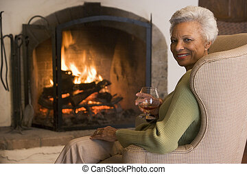 Woman in living room with drink smiling