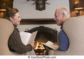 Couple sitting in living room by fireplace with books smiling