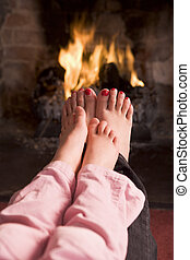 Mother and daughter\\\'s Feet warming at a fireplace