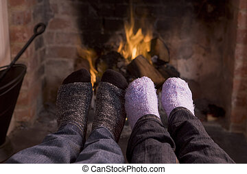 Couples feet warming at a fireplace
