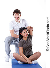 Woman with personal trainer - A young woman stretching with...